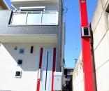 赤のアクセントカラーで空に映える門柱