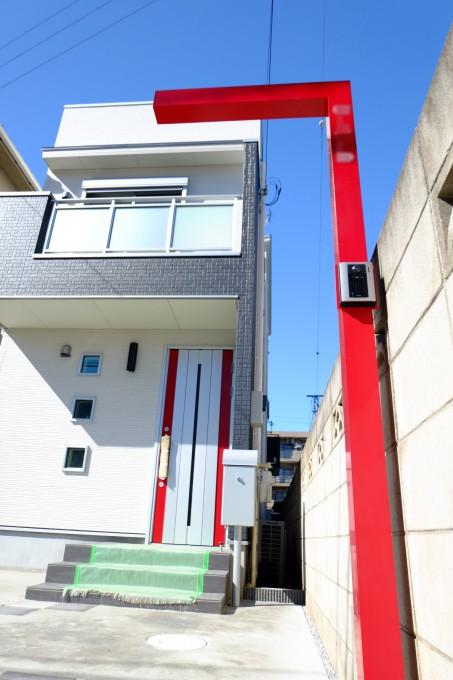 赤のアクセントカラーで空に映える門柱 写真
